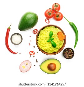 Bowl with tasty guacamole and ingredients on white background