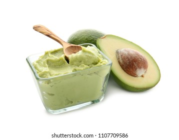 Bowl with tasty guacamole and ripe avocados on white background