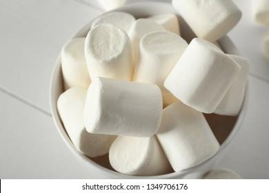 Bowl with tasty marshmallows on white table, closeup