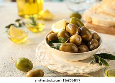 Bowl with tasty olives on grey background