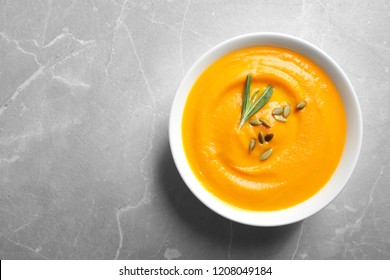 Bowl of tasty pumpkin soup and space for text on gray table, top view