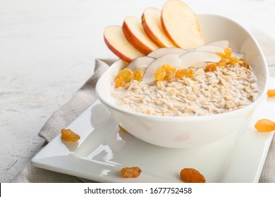 Bowl with tasty sweet oatmeal on white background