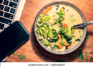 Bowl of Thai curry soup next to laptop and phone.  Work from home or home office concept.