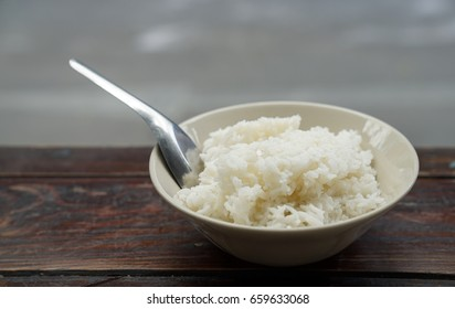 A bowl of Thai jasmine rice on wooden table.