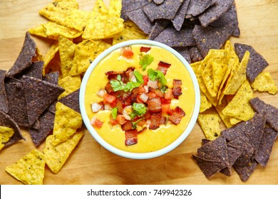 Bowl of Thick Creamy Queso Cheese Dip with Bacon, Peppers and Tomatoes and Tortilla Chips