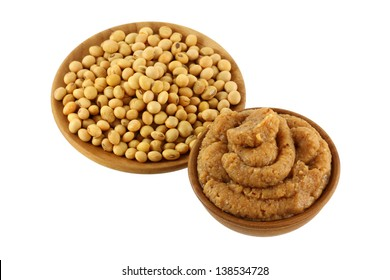 A Bowl of thick Japanese Miso Paste (fermented soybeans) next to dried Soybean seeds isolated on white background