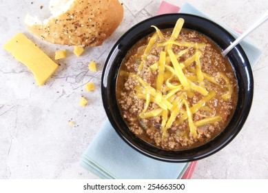 Bowl of thick, Texas Style chili with meat, beans and vegetables sits on cloth napkins with rustic bread and hard cheese beside it on a white marble counter or table.