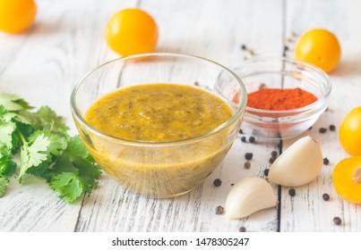 Bowl of tkemali - Georgian plum sauce with the ingredients