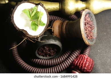 bowl with tobacco for hookah. fruits on a black background. smoking nargile