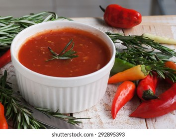 bowl of tomato hot sauce with peppers, rosemary and cutlery