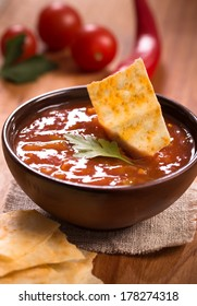 Bowl of tomato sauce with chips