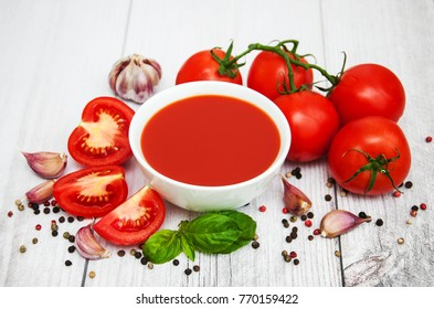 Bowl with tomato sauce and fresh tomatoes on a table