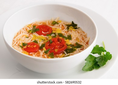 a bowl of tomato vermicelli soup decorated with parsley leafs