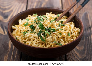 bowl of traditional Chinese noodles and chopsticks on wooden background, closeup
