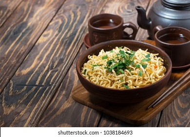 bowl with traditional Chinese noodles and tea on wooden background, top view