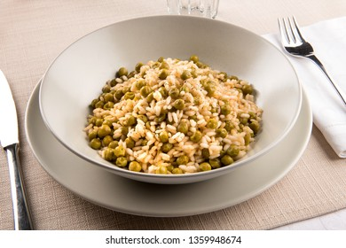Bowl of traditional Risi e Bisi from the Veneto, Italy made with stock, rice, seasoning and fresh green peas, served at table with utensils