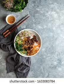 bowl of traditional Vietnamese noodle salad - Bun Bo Nam Bo, with beef, rice noodles, fresh herbs, pickled vegetables and fish sauce