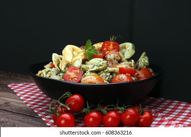 Bowl of tricolor tortellini pasta salad with tomatoes and onions on dark wood table background