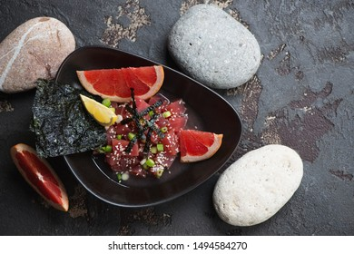 Bowl of tuna ceviche with grapefruit juice, flatlay on a brown stone background with pebbles, studio shot