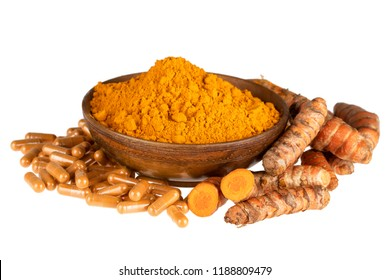 Bowl of Turmeric powder with roots and capsules, isolated on a white background