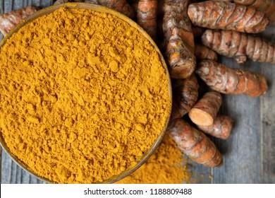 Bowl of turmeric powder with turmeric roots flat lay