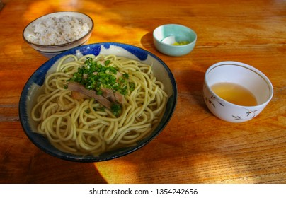 Bowl with udon noodles, pork and green onions, vegetable, and white Japanese rice, with side dishes of pickes, dashi and rice. Lunchtime in Kanazawa city, Ishikawa Prefecture, Western Japan.