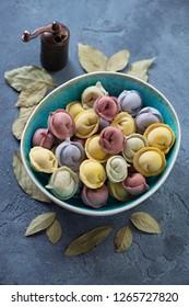 Bowl of uncooked colored dumplings pelmeni over blue stone background, vertical shot