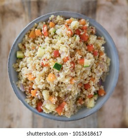Bowl of vegan bulgur pilaf with carrots, red peppers, onions and zucchini.