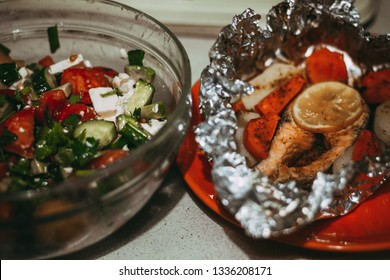 bowl with vegetable salad and grilled salmon steak in a pile, standoff for vegetarians and those who eat meat