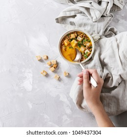 Bowl of vegetarian pumpkin carrot soup served with croutons and onion on textile linen over gray concrete background. Child hands. Top view with space. Square image