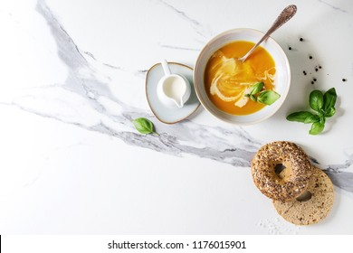 Bowl of vegetarian pumpkin carrot soup served with herbs, spoon, jug of cream, bagel bread, black pepper, salt over white marble texture background. Flat lay, copy, space