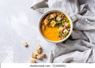 Bowl of vegetarian pumpkin carrot soup served with croutons and onion on textile napkin over gray concrete background. Top view with copy space