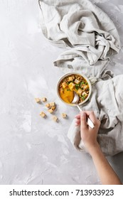 Bowl of vegetarian pumpkin carrot soup served with croutons and onion on textile linen over gray concrete background. Child hands. Top view with space