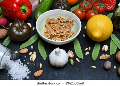 A bowl of walnuts, a lemon, a pepper, tomatoes, a garlic, a cucumber, a strawberry,a radish,Romaine,walnuts,different nuts,pea pods,a tangerine & a glass jar with spilled salt lying on a black surface