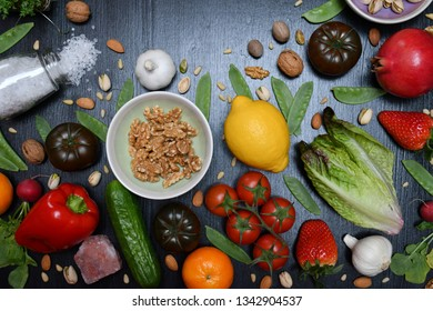A bowl with walnuts, a lemon, a Romaine,tomatoes,a pomegranate,tangerines,garlics,strawberries,radishes,a pepper,Cress,a cucumber,different nuts,pea pods,a glass jar with salt lying on a black surface