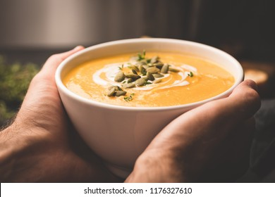 Bowl of warm pumpkin soup in hands. Holding bowl of vegan pumpkin soup. Comfort food. Toned image, selective focus
