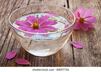 bowl of water and floating flower sitting on wooden table
