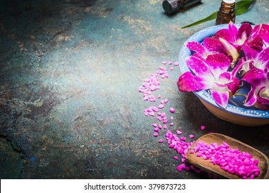 Bowl with water and purple orchid flowers on dark background with shovel of sea salt. Spa, wellness or body care concept.