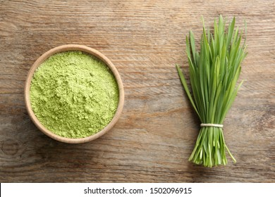Bowl of wheat grass powder and green sprouts on wooden table, flat lay