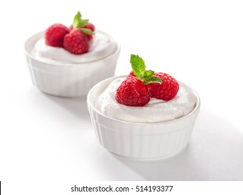 bowl of whipped cream with raspberries and  mint leaves  close-up on white background