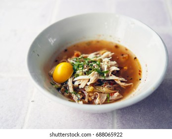 A bowl of white noodle soup with shredded chicken and boiled egg (spicy tom yum) on table  background, Traditional Thai food recipe, Popular street food in Thailand.