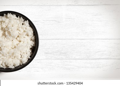 Bowl of white rice on white wood grain background with copy space.