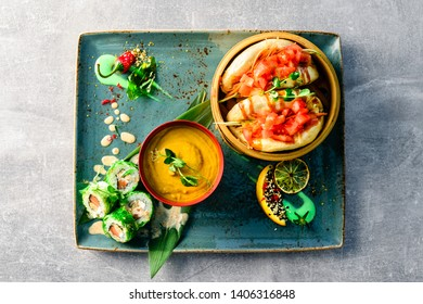 Bowl of wonton noodle soup and baozi on serving tray, flatlay on a dark grey stone background, copy space, asian food Bao buns and carrot soup, steam bun Bao Top view