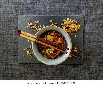 Bowl of yakisoba with fried onion from above with copy space.