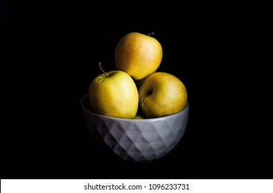 Bowl of yellow apples. On black background. a