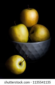 Bowl of yellow apples. On black background.
