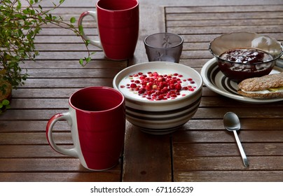 Bowl with yogurt and berries on the wooden table. Spoon and cups are next to bowl.
