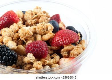 A bowl with yogurt, granola and fruits.