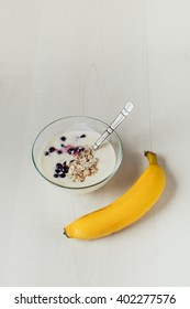 A bowl  with yogurt, oat flakes, berries, spoon and banana