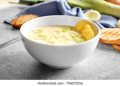 Bowl of yummy potato soup with leek and crisps on table